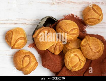 From above view of baked round buns laid on brown napkin on wooden background