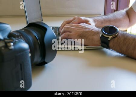 man processes photos on laptop after downloading them from camera