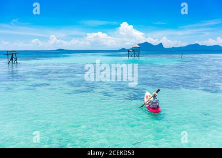 Back view male boating on canoe with paddle on amazing azure sea and blue sky in Malaysia - Stock Photo