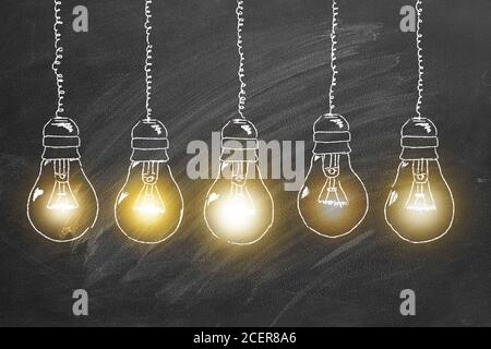 Row of  tungsten light bulbs drawn in chalk on a blackboard. Concept of brainstorming  process.