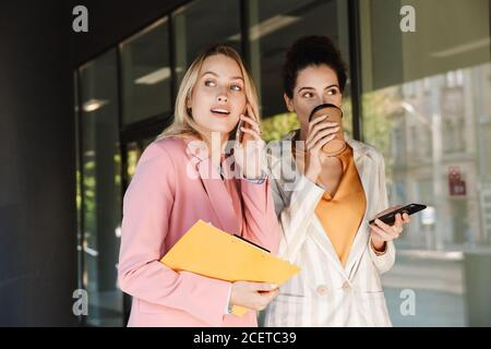 Two beautiful smiling young businesswomen walking outdoors at the city streets, talking while drinking coffee and using mobile phones