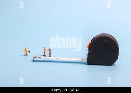 Meter stick and worker on blue background