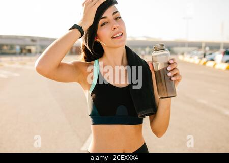 Positive young slim female in sportswear wiping head with towel and drinking fresh beverage from plastic bottle while relaxing after hard training on street