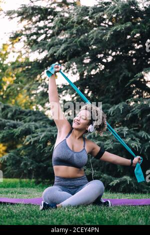 Full body positive young fit female with headphones sitting with legs crossed on grass and stretching arms with resistance band during fitness training in summer park