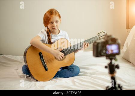 portrait of beautiful cute caucasian child girl blogger playing guitar at camera. adorable girl sit showing, performing new melody for subscribers. vl