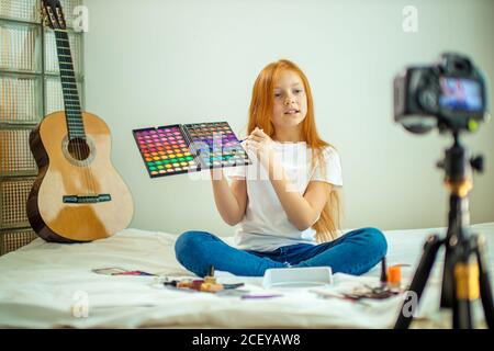 portrait of little caucasian blogger child interestingly talk about cosmetics, cute girl with long red hair present beauty things, sit in front of cam