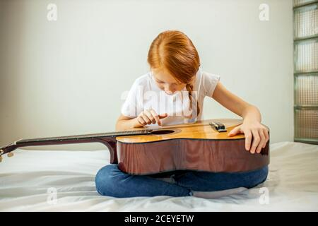 cute adorable child blogger play guitar, talk at camera how she learned playing acoustic guitar, she is self-taught