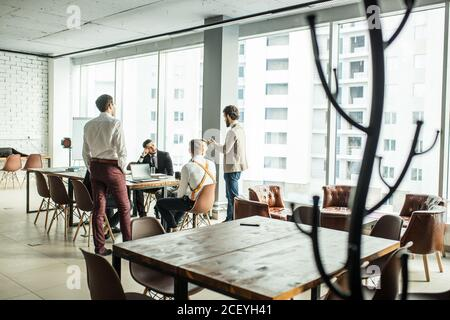 confident business people coworking in office, wearing formal clothes, elegant tuxedo. men hold meeting in boardroom for discussion and cooperation. b - Stock Photo