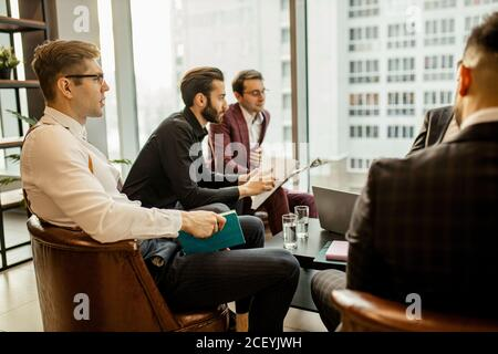 young caucasian successful business men hold meeting for making useful cooperation between companies, developing business strategies together in offic Stock Photo