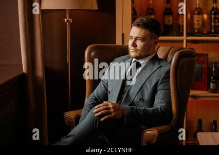Portrait of young purposeful man looks aside with a calm face, sits in glorious armchair with crossed legs, puts right palm on knee, posing against ba