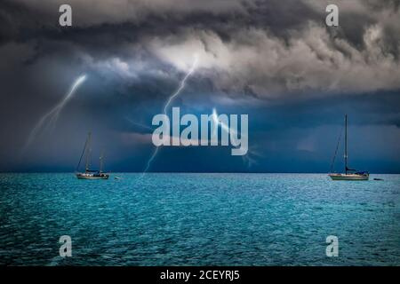 Yachts are at sea in a storm. Lightning flashes from the sky into the water. It's in Sardinia, Italy. It's raining from black clouds. - Stock Photo