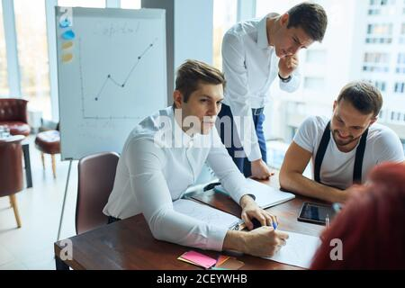 Successful young team of caucasian coworkers making great creative business discussion in modern coworking office, panoramic windows background