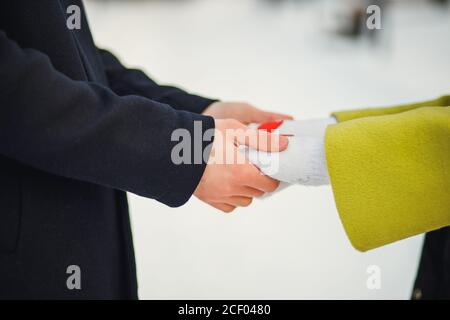 close-up hands of couple in love, man and woman have romantic date at winter street. caring man hold woman's hands. love concept. outdoors - Stock Photo