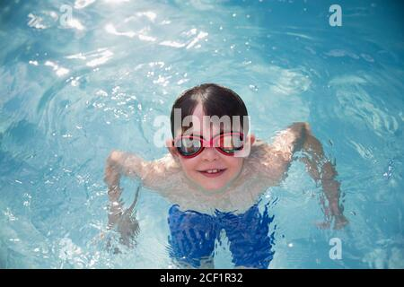 Portrait smiling boy in goggles swimming in sunny swimming pool - Stock Photo