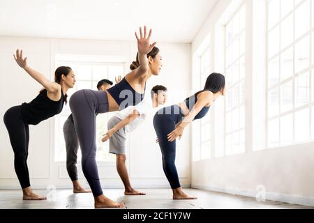 Group of sporty attractive asian people wearing sportswear bra pants practicing yoga lesson on Uttanasana pose Standing Forward Bend with instructor