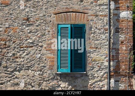 Italian Window with Wooden Shutters in a brick wall