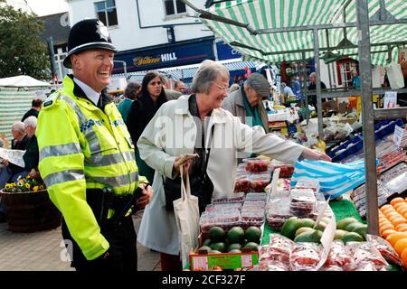 Policeman talking to members of the public in local market; Knaresborough; Scarborough; Yorkshire UK