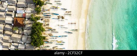 Stunning aerial view of a fishing village with houses and boats on a white sand beach bathed by a beautiful turquoise sea. Tanjung Aan Beach, Lombok. - Stock Photo