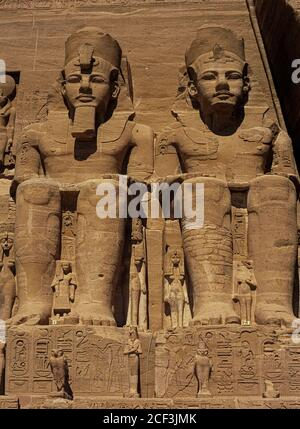 Two of the four seated colossi, each 20 m (66 ft) high, of the long-ruling 19th Dynasty New Kingdom Pharaoh, Ramesses II, that dominate the façade of the Great Temple he built in the 13th Century BC at Abu Simbel, Aswan Governate, Egypt.  Smaller effigies of his wives and children stand alongside the colossi and between their feet.  The two massive rock temples at Abu Simbel stand on the western bank of Lake Nasser in Nubia, Upper Egypt.  They were relocated in 1968 to an artificial hill high above the Aswan High Dam reservoir, to stop them being engulfed by the lake's rising waters. - Stock Photo