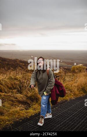 Woman walking on hillside in gloomy day - Stock Photo
