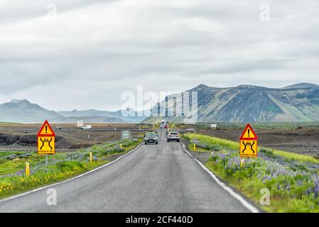 Vik, Iceland - June 14, 2018: Colorful signs for narrow road bridge in Iceland with flower meadow field with cars passing in traffic on ring road trip - Stock Photo