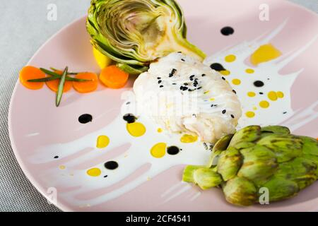 Stewed hake Provencal. Recipe: 250gr of hake fillet braise for 20 minutes with cream, garlic, olive oil, salt, black pepper. Serve with boiled articho - Stock Photo