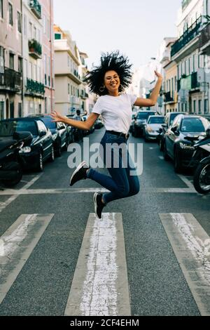 Young cheerful African American woman in jeans and white t-shirt jumping for joy in city street on daytime