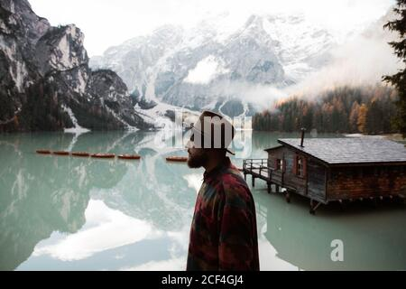 Back view of anonymous hipster man traveler in casual wear standing and delighting in view of wooden house on turquoise lake with foggy Dolomites mountains on background at Italy - Stock Photo