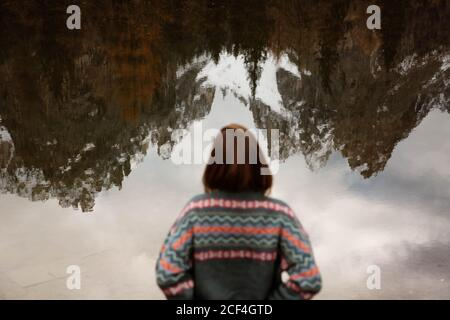 Back view of anonymous woman traveler in casual wear standing and delighting in view of lake with foggy Dolomites mountains on background at Italy