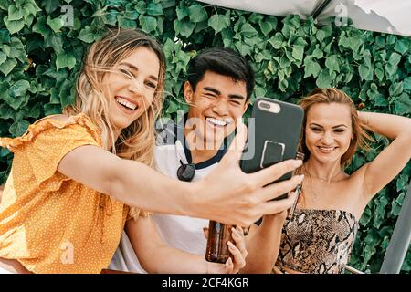 two women and a man drinking beer and taking selfies