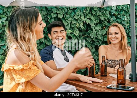 two young women and a man laughing and having a good time