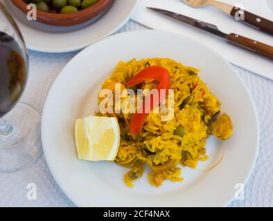 Traditional Valencian paella de mariscos served on white plate with lemon slice Stock Photo