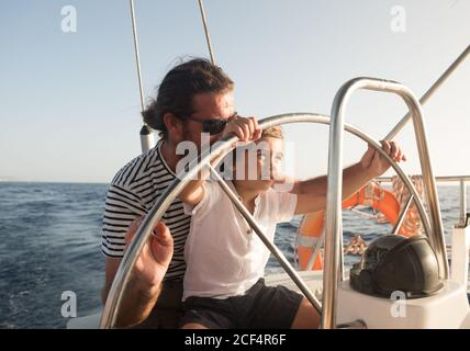 Father and son floating on expensive boat on sea and blue sky in sunny day