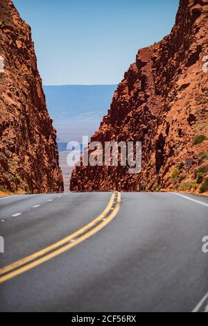 Empty scenic highway in Arizona, USA. Road in mountains. A long straight road leading towards a rocky mountain.