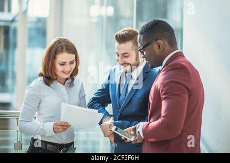 businessman holding papers hands and smiling.Young team of coworkers making great business discussion in modern coworking office