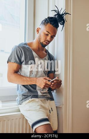 Young African American man with creative hairstyle standing leaning on windowsill and browsing in mobile phone