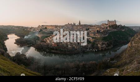Panoramic view across river of old city Toledo in Spain with medieval castles and fortresses at sunset time with cloudy sky and reflection in river water