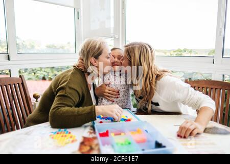 Middle aged woman with little girl and adult daughter having fun and playing board game hugging and kissing while sitting at round table on terrace