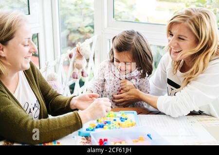 Middle aged woman with little girl and adult daughter having fun and playing board game while laughing and tickling each other at table