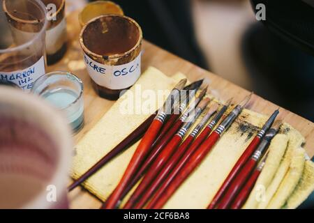 Paintbrushes on table among art tools Stock Photo