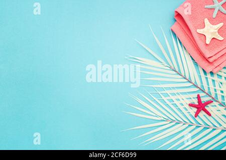 Top view composition with colorful starfish placed on pink towel and palm leaves against blue background representing summer holiday concept