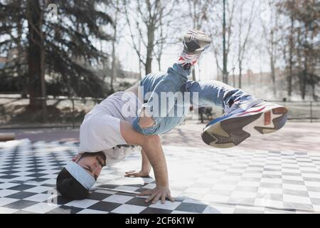 Young bearded guy in casual wear doing headstand in park in sunny weather