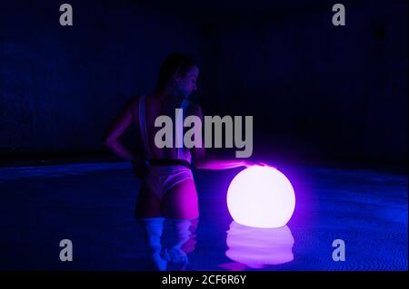 Back view of slim female in swimsuit standing in dark thermal bath pool with luminous ball on water