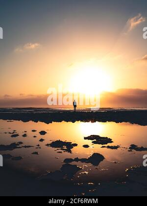 Silhouette of anonymous person standing on shore near calm water against sundown sky in evening on Fuerteventura Island, Spain - Stock Photo