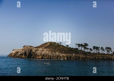 Lonely fishing boat moving on bay with tranquil water against rocky shore with tall evergreen trees at foot of hill under clear blue sky in Spain