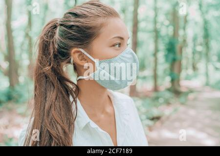 Face mask of cotton fabric are breathable for skin. Asian woman wearing corona virus mouth covering walking outdoors in woods