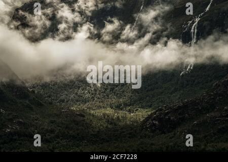 White cloud haze over green plain at foot of gloomy high mountains in Tortel - Stock Photo