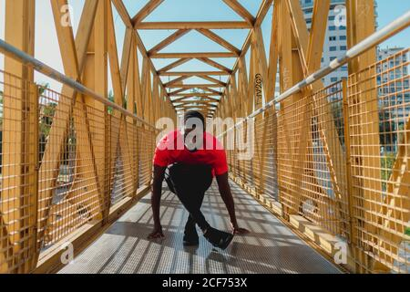 Sporty black man in red t-shirt stretching on big iron bridge in bright day
