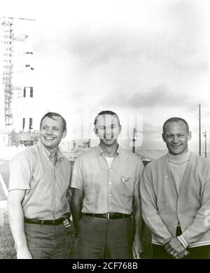 NASA's Apollo 11 flight crew, Neil A. Armstrong, commander; Michael Collins, command module pilot; and Buzz Aldrin, lunar module pilot stand near the Apollo/Saturn V space vehicle that would eventually carry them into space on July 16,1969. - Stock Photo
