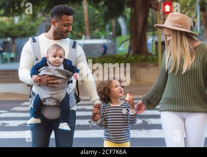 Happy young multiracial parents with little daughter eating apple and cute infant boy crossing road on zebra while walking in city in summer day